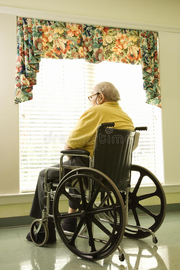 Elderly Man in Wheelchair by Window. Elderly man in wheelchair sits and looks out of large window. Vertical shot stock photography