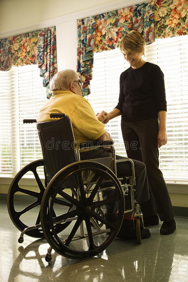 Elderly Man in Wheelchair and Young Woman. Elderly man in a wheelchair and a young woman stand by a window and hold hands. Vertical shot royalty free stock photos