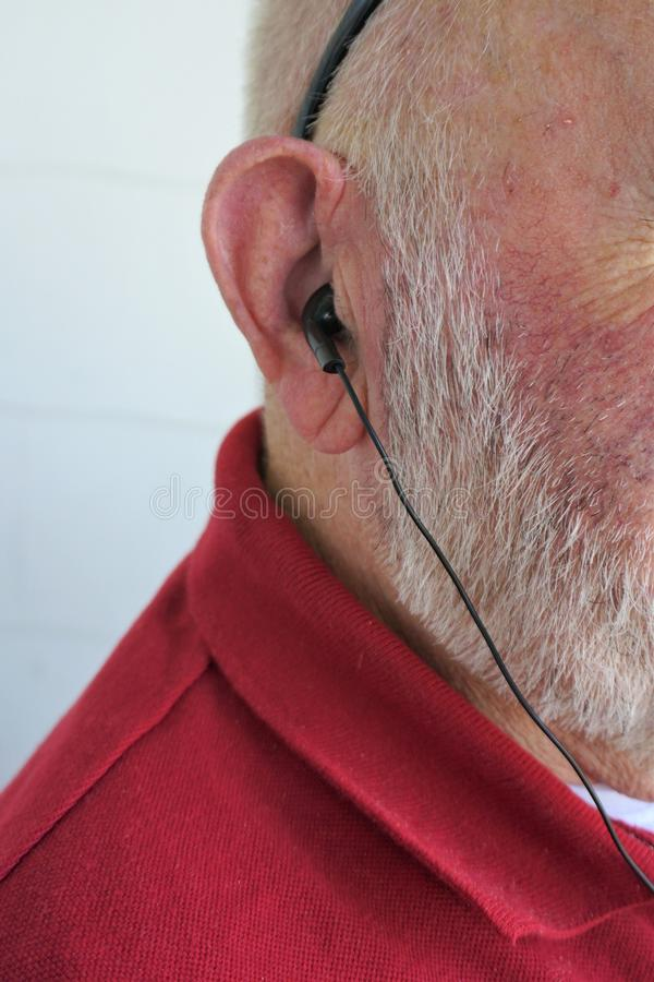 Aged gentleman listens through earbuds royalty free stock photo