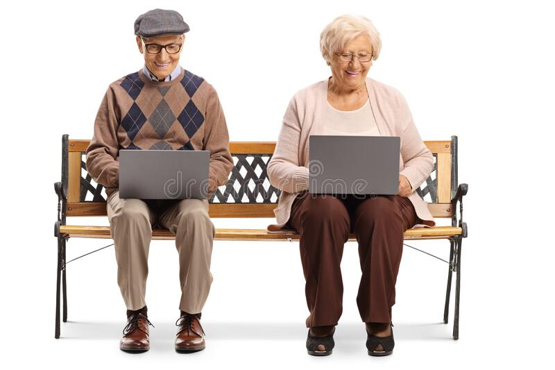 Elderly man and woman on a bench with laptop computers stock photo