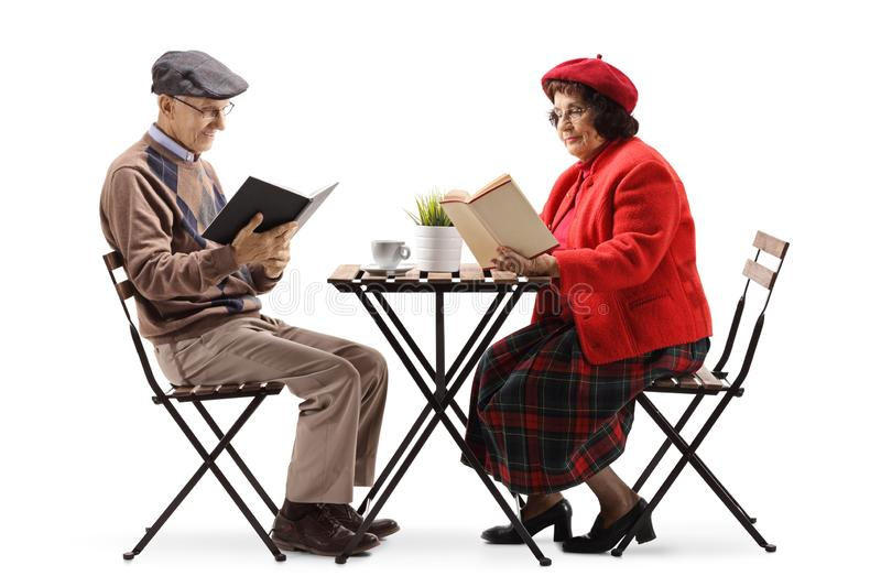 Elderly man and woman at a cafe reading books royalty free stock photo