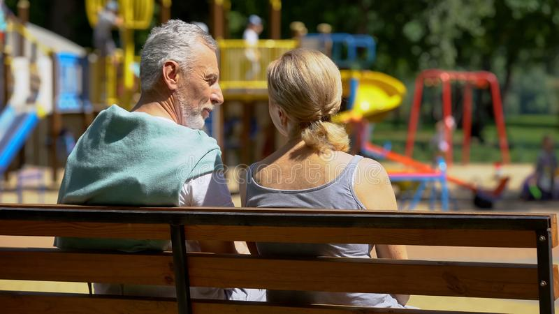Elderly man and woman communicating on bench in park, watching grandchildren stock images