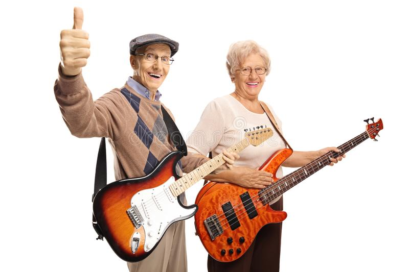 Elderly man and woman with electric guitars showing thumbs up. Elderly men and women with electric guitars showing thumbs up isolated on white background royalty free stock photo