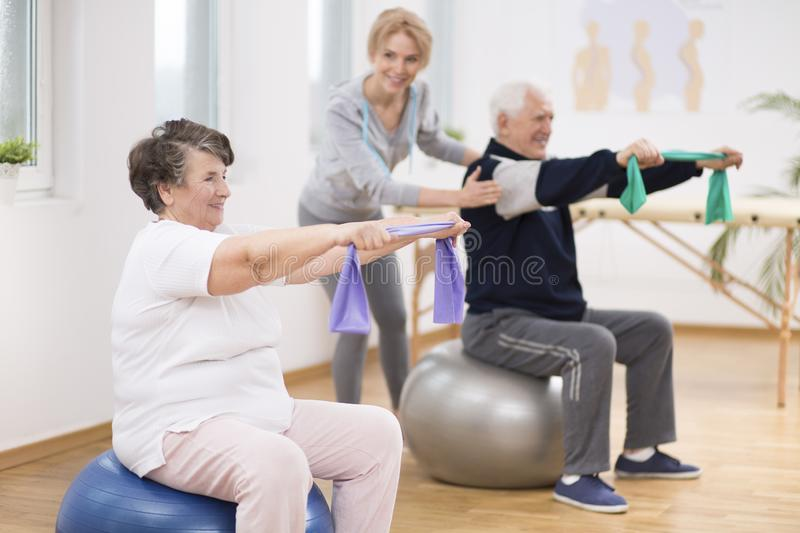 Elderly man and woman exercising on gymnastic balls during physiotherapy session at hospital royalty free stock photo