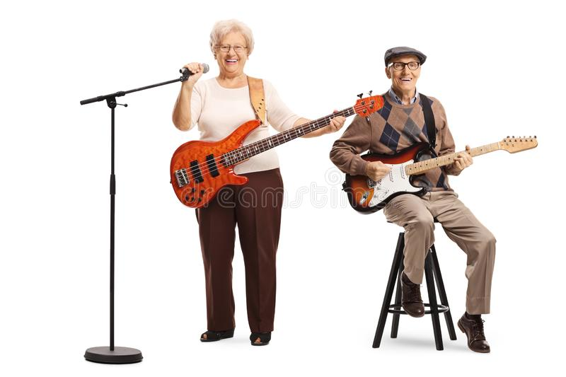 Elderly man and woman with guitars and a microphone. Full length portrait of an elderly men and women with guitars and a microphone isolated on white background stock images