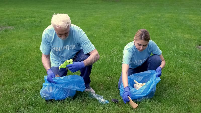 Elderly man and woman picking litter smiling each other, environmental activism. Stock photo stock image