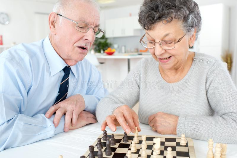 Elderly man and woman playing chess at home royalty free stock photos