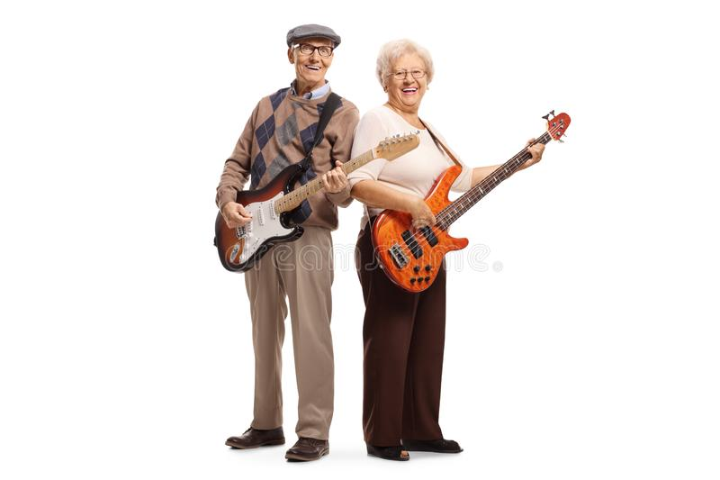 Elderly man and woman playing electric guitars. Full length portrait of an elderly men and women playing electric guitars isolated on white background royalty free stock images