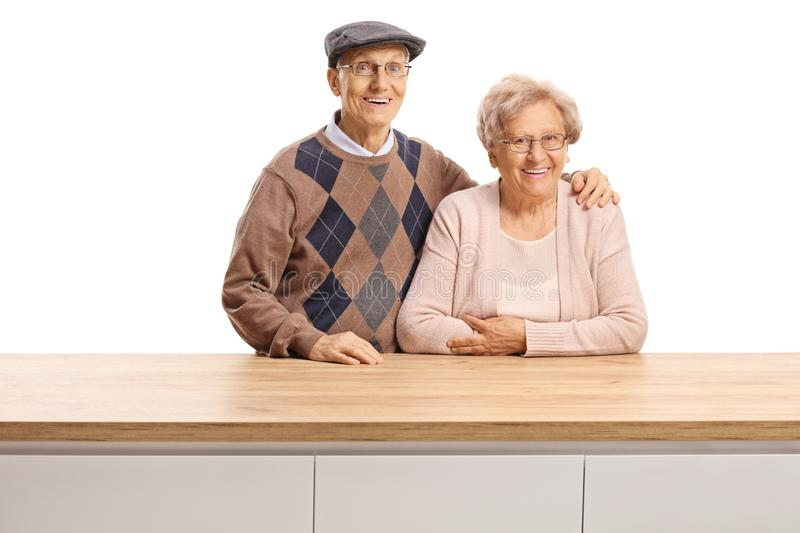 Elderly man and woman posing behind a wooden counter. Elderly men and women posing behind a wooden counter isolated on white background stock photo