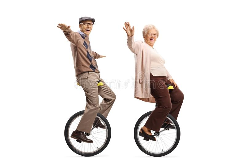 Elderly man and woman riding unicycles and smiling at the camera. Full length shot of elderly men and women riding unicycles and smiling at the camera isolated stock images