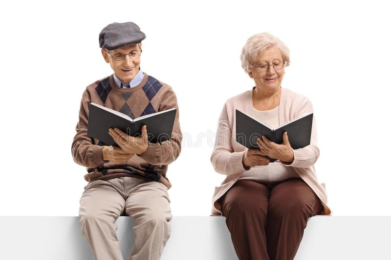 Elderly man and woman seated on a panel reading books. Elderly men and women seated on a panel reading books isolated on white background royalty free stock photography