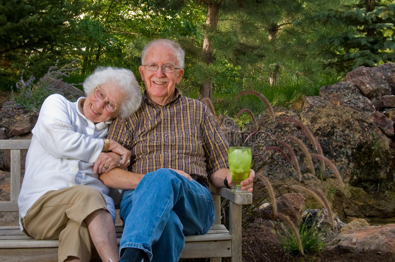 Elderly man and woman sitting on stock image