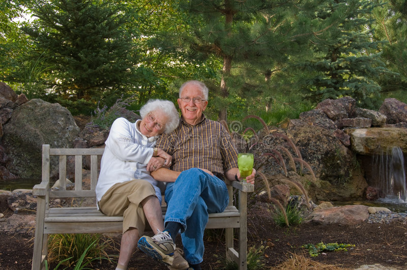 Elderly man and woman sitting on a bench stock photos
