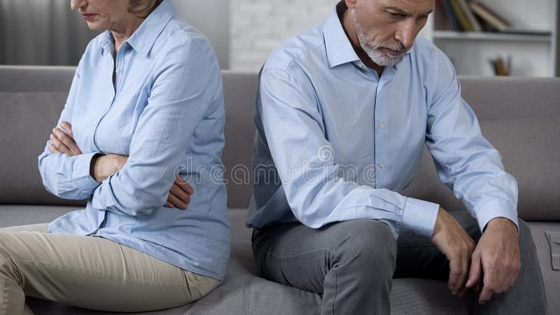 Elderly man and woman sitting on sofa turned away from each other, family crisis stock photo