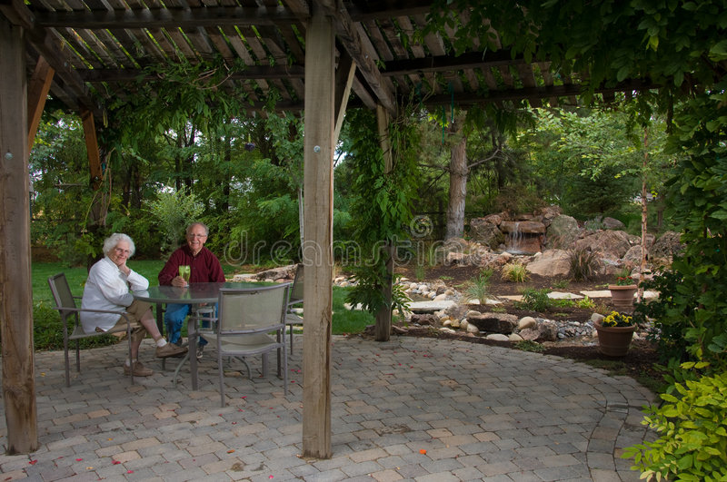 Elderly man and woman sitting in their yard stock photos