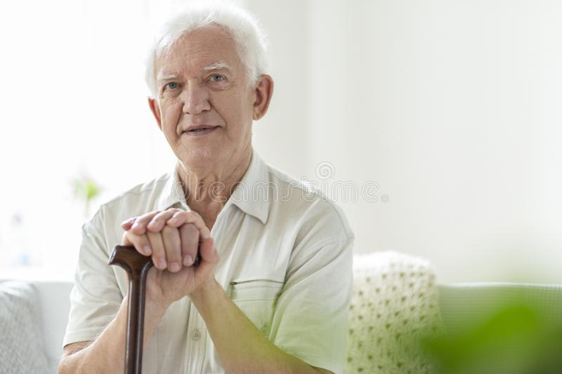 Elderly man with wooden walking stick in the nursing house royalty free stock image