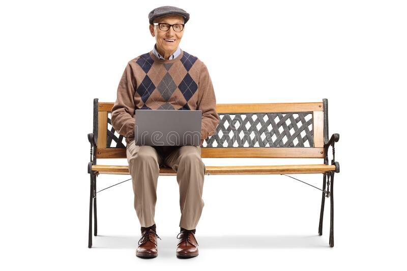 Elderly man working on a laptop and sitting on a bench royalty free stock image