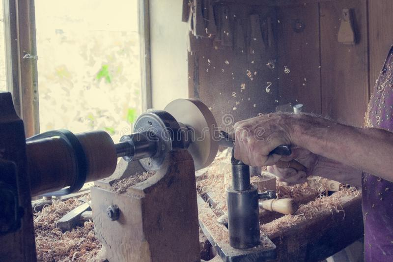 Elderly man works on a carpentry machine, retro style, dust and shavings on a table.  royalty free stock images