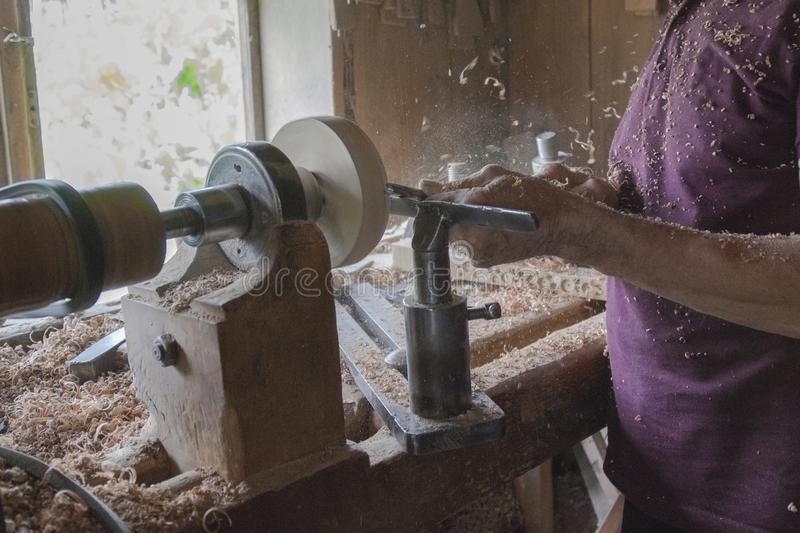 Elderly man works on a carpentry machine, retro style, dust and shavings on a table.  stock images