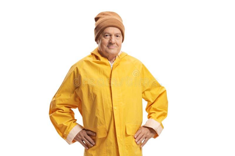 Elderly man in a yellow raincoat wearing a warm hat stock image