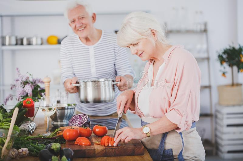 Elderly marriage on culinary workshop. Cooking a vegan meal together royalty free stock photo