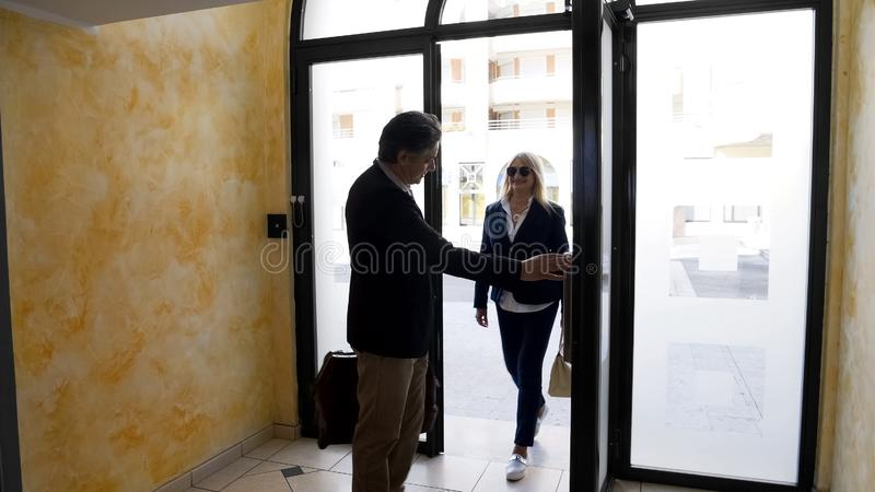 Elderly married couple entering multi-store building to view apartment for rent stock image