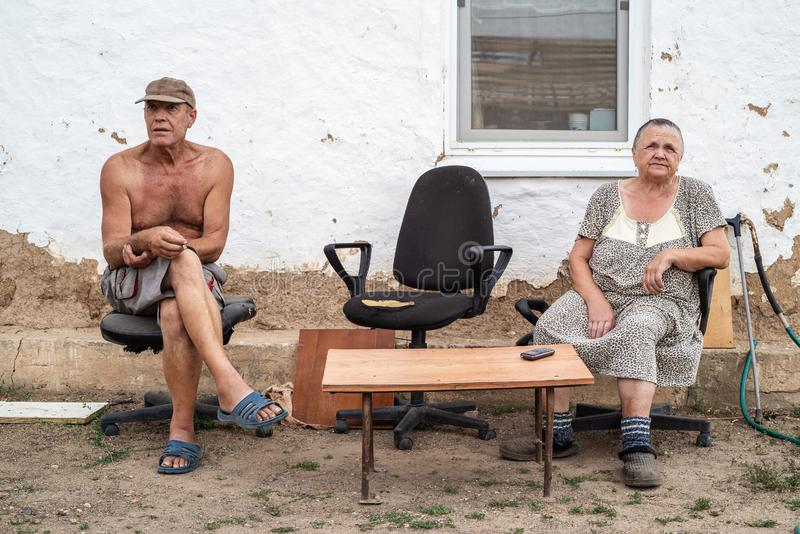 Elderly married couple in the yard of a rural house. Photo taken in Russia, in the countryside royalty free stock images