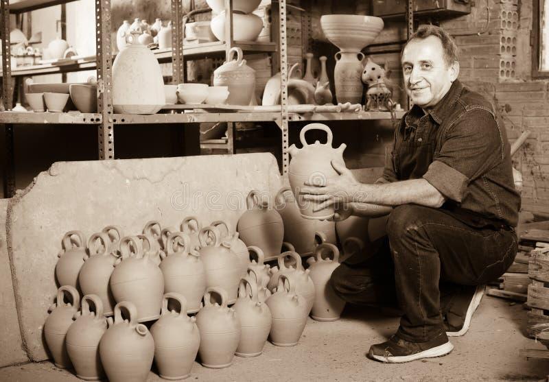 Elderly master at pottery workshop. Friendly smiling elderly man holding pottery at ceramic workshop royalty free stock image