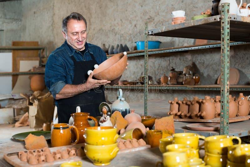 Elderly master at pottery workshop. Joyful smiling elderly man holding pottery at ceramic workshop stock photography