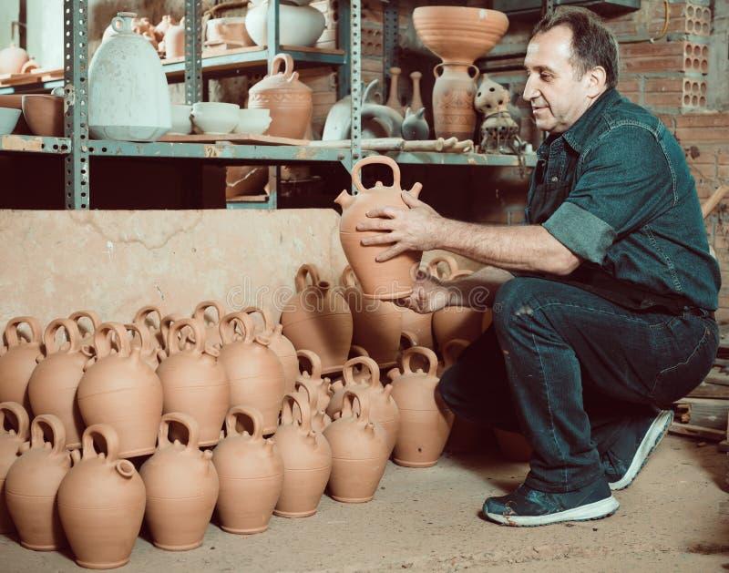 Elderly master at pottery workshop. Elderly man holding pottery at ceramic workshop stock images