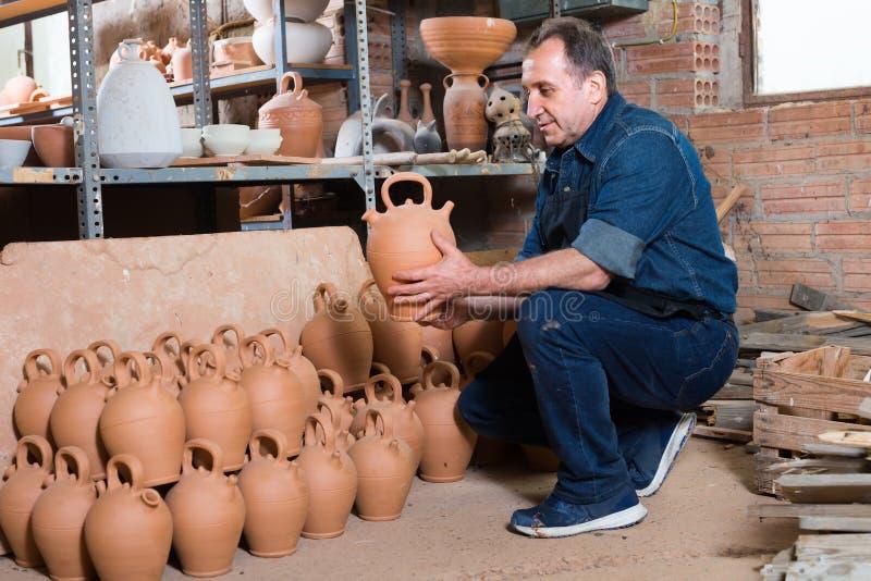Elderly master at pottery workshop. Senior man holding pottery at ceramic workshop royalty free stock image