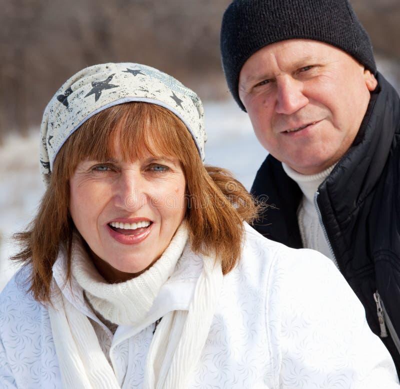 Elderly mature people. Happy seniors couple in winter park. Elderly mature people stock photo