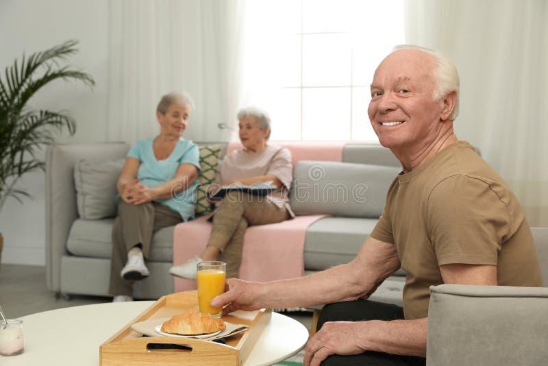 Elderly man having breakfast at nursing home. Assisting senior people stock images