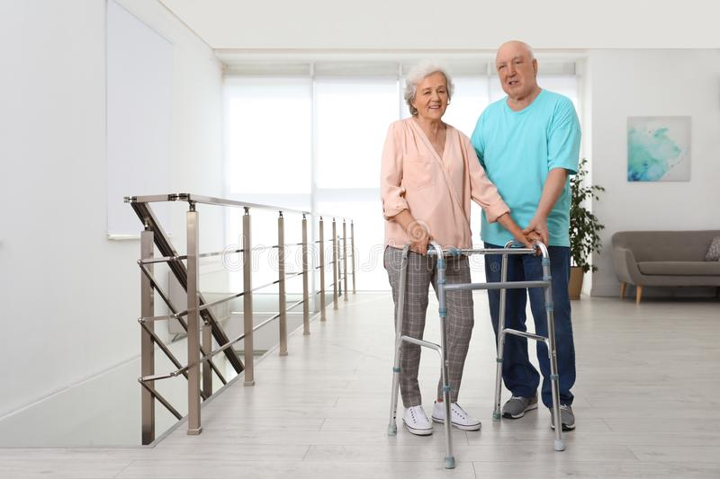 Elderly man helping his wife with walking frame royalty free stock image