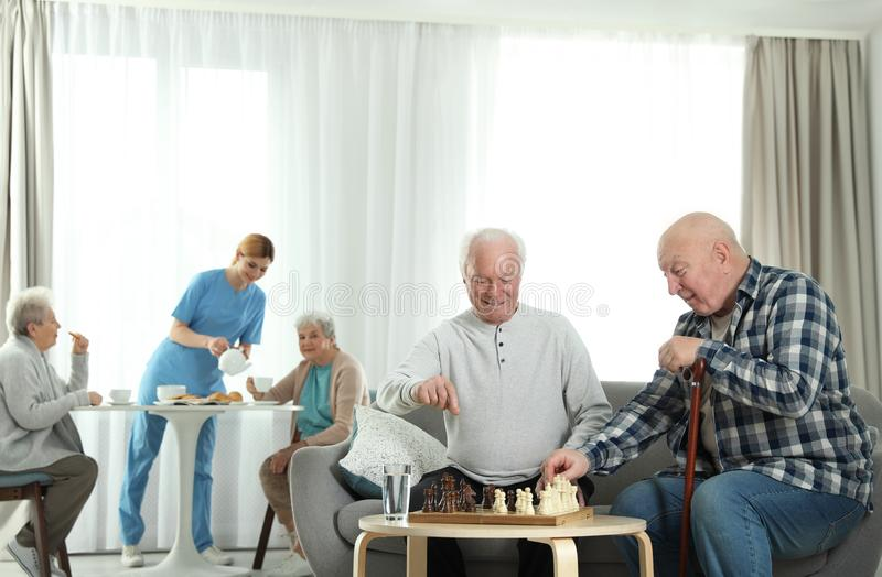 Elderly men playing chess while nurse serving breakfast to women. Assisting senior people royalty free stock photos