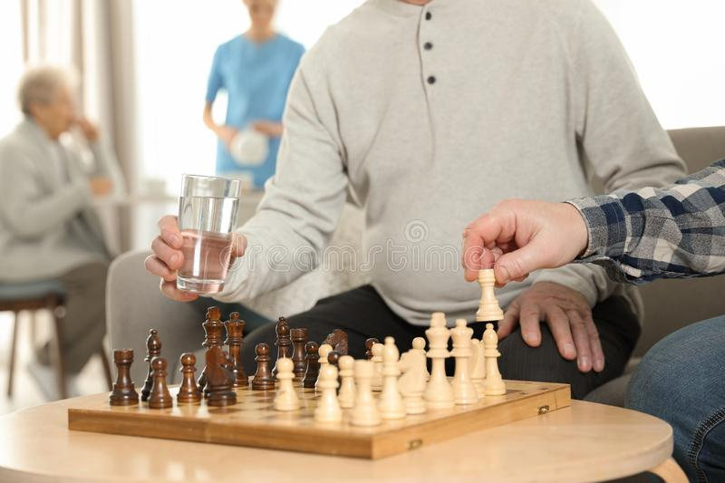 Elderly men playing chess at nursing home. Assisting senior people stock images