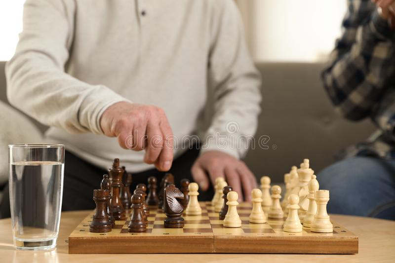Elderly men playing chess at nursing home. Assisting senior people stock image