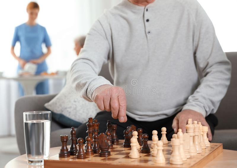 Elderly men playing chess at nursing home. Assisting senior people stock photography
