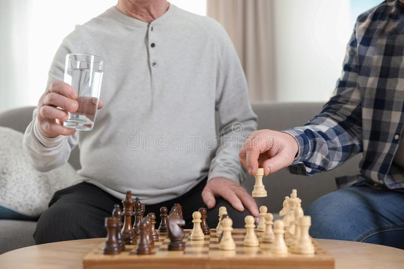 Elderly men playing chess at nursing home, closeup. Assisting senior stock photo