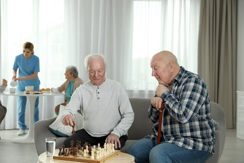 Elderly men playing chess at nursing home royalty free stock photography