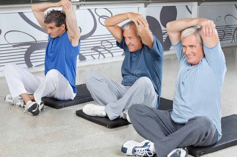 Elderly men stretching in fitness. Center on gym mats stock photos