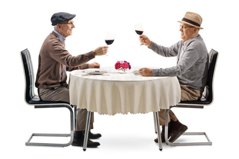 Elderly men toasting with red wine at a table. Isolated on white background royalty free stock image