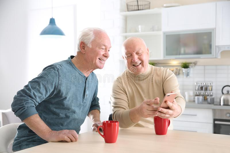 Elderly men using smartphone at table. In kitchen royalty free stock image