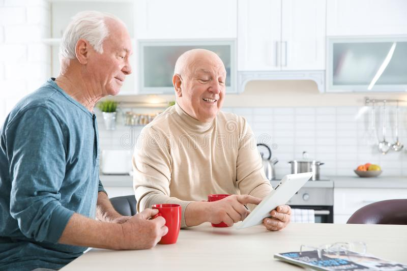 Elderly men using tablet PC at table. In kitchen stock photo