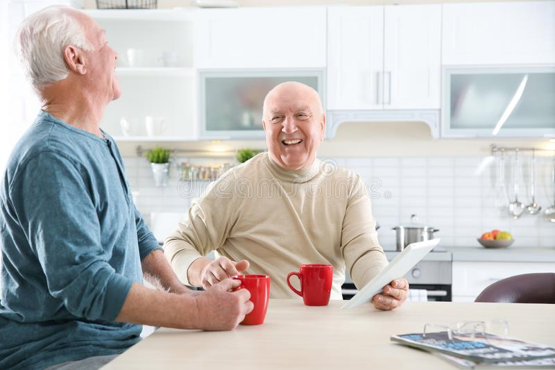 Elderly men using tablet PC at table. In kitchen royalty free stock photo