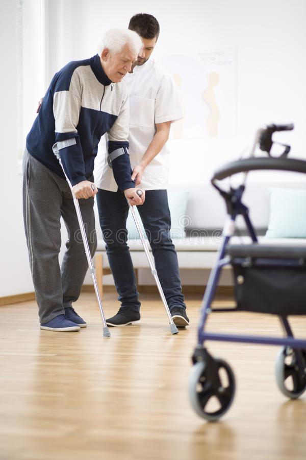 Elderly man walking on crutches and a helpful male nurse supporting him stock photos