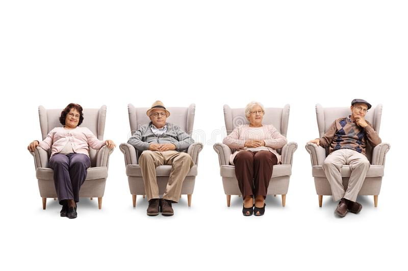 Elderly men and women sitting in armchair and looking at the cam. Era isolated on white background royalty free stock photo