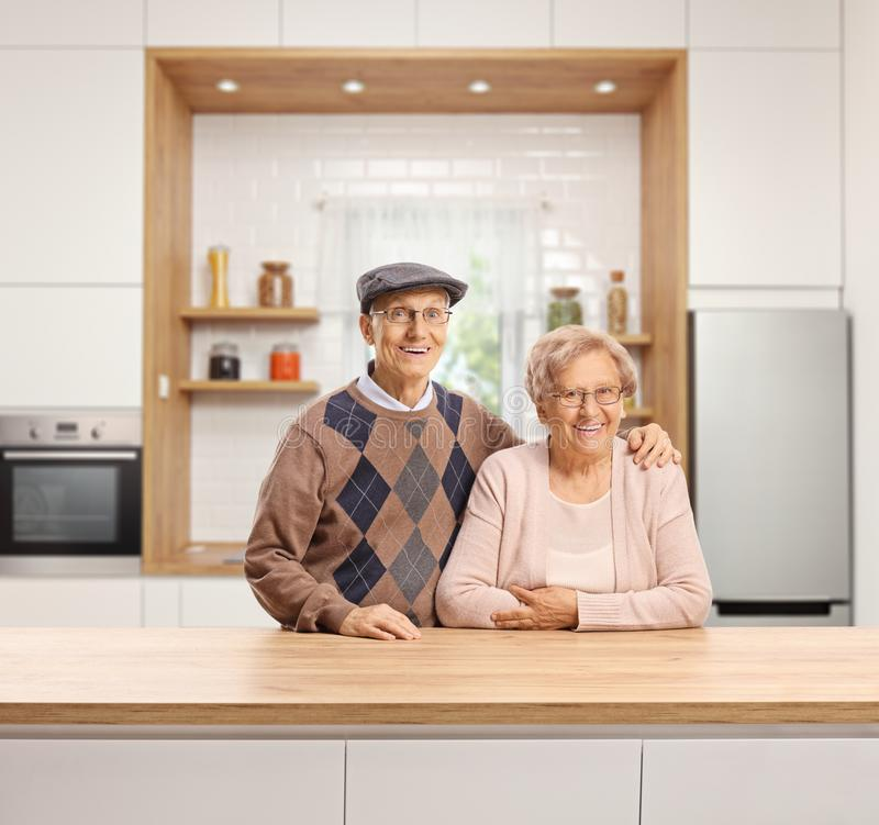 Elderly man and woman standing in a kitchen. Elderly men and women standing in a kitchen and smiling stock photo