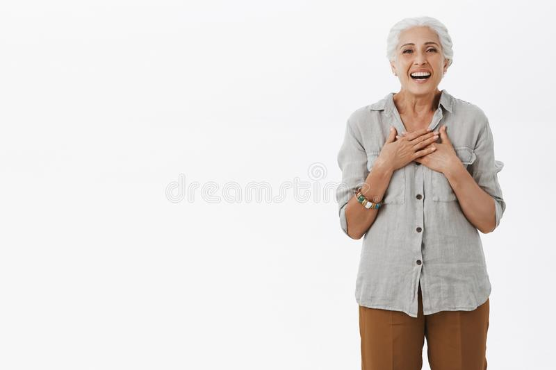 Elderly mother pleasantly surprised seeing grandchildren visiting her. Portrait of delighted happy cute and kind old stock photo