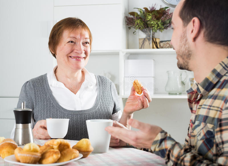 Elderly mother and son breakfast. Smiling elderly mother and son having breakfast and warmly talking at table at home stock photos